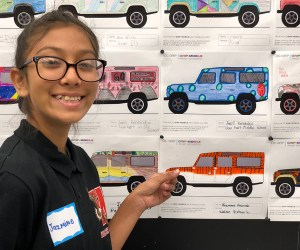 Student Jazmine Alvarado points to her tiger design for an SUV