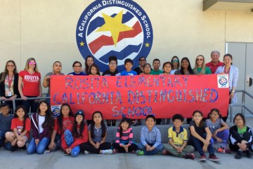 Rosita Elementary students holding a banner in front of the Distinguished Schools banner
