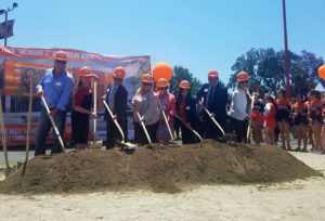 a line of dignitaries hold shovels over a patch of dirt