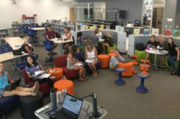 teachers sit inside a library collaborating on lessons