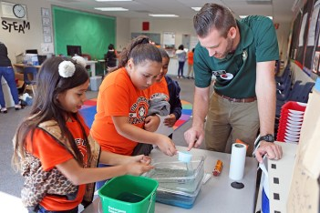 a teacher leads students in science experiment