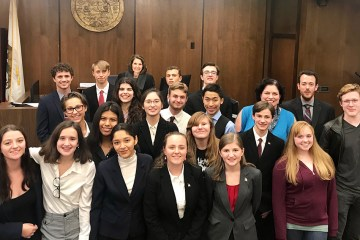 Students pose for photo in a courtroom
