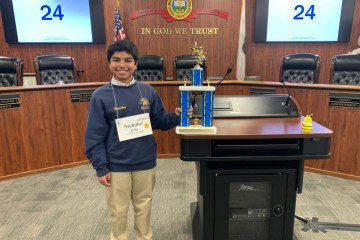 Eighth-grader Nicholas D'Sa holds trophy