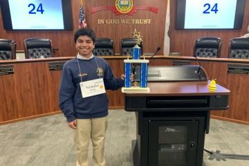 Eighth-grader Nicholas D'Sa holds trophy