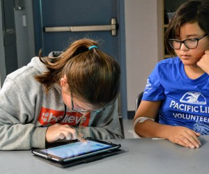 two girls work on an ipad coding project