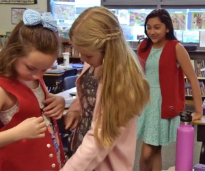 students in a classroom try on vests