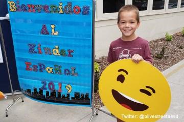 student holds up emoji at school