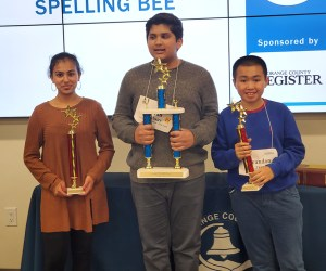 spelling bee students hold trophies