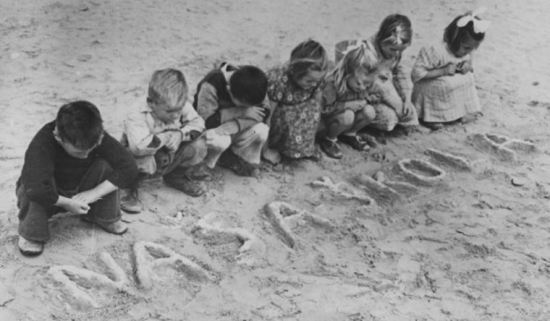 "Young children at a World War II refugee camp in Tolumbat, Egypt write the words ""naša škola,"" or ""our school,"" into the sand. 
