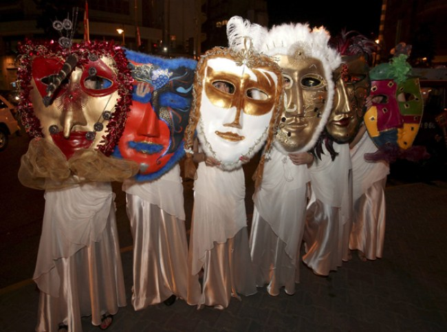 Students hide their faces with giant masks during a celebration of Saint Barbara's day in Beirut | Source: Reuters/Xinhua