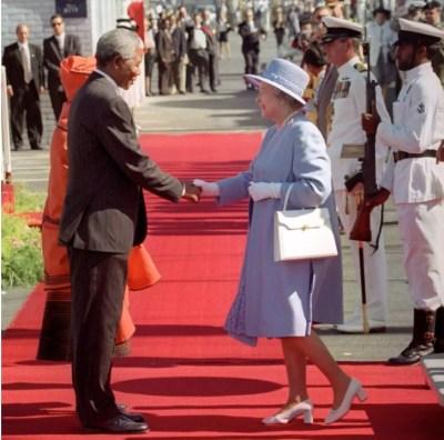 Президент Южной Африки Нельсон Мандела приветствует Королеву Елизавету II, когда она шагает от королевской яхты Britannia в Кейптауне в официальном начале 1995 года ее первого визита в страну с 1947 года
