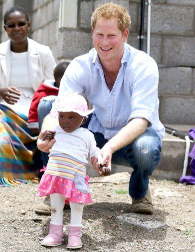 Принц Гарри играл с красивой девочкой во время посещения школы Лесото, финансируемой его благотворительной Sentebale в декабре 2014 года.