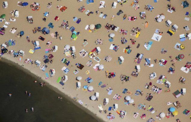 Люди плавают и загорают в жаркий солнечный летний день на пляже Wannsee под Берлином, Германия, 4 июля 2015. Немецкая метеослужба (DWD) консультируется относительно высоких температур на 'рекордных уровнях' в южной и западной Германии на этой неделе. (АГЕНТСТВО РЕЙТЕР/ГАННИБАЛ HANSCHKE)