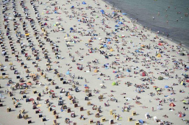 """Люди сидят в шезлонгах, наслаждаясь жаркой солнечной погодой на Балтийском море курорт Травемюнде, северная Германия, 4 июля 2015 года. Немецкая служба погоды (DWD) советует при высоких температурах в """"рекордные уровни» в южной и западной Германии на этой неделе. (REUTERS / Fabian Bimmer)"""