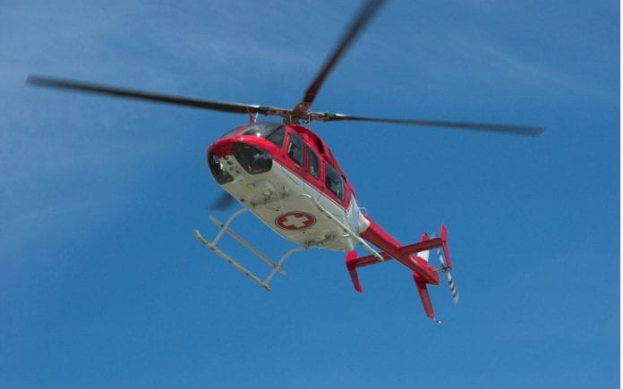 closeup-of-flying-red-helicopter-in-contrast-with-blue-sky-picture-id174905087-1-696x435