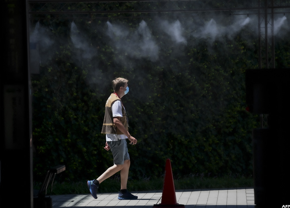 A photographer walks under a disinfection system installed at the International Press Centre for the 2020 Tokyo Olympics in Tokyo