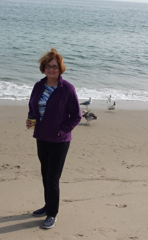 Woman with wind-blown hair standing on beach near sea gulls