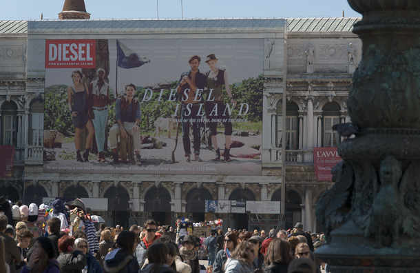 Tourists in the Piazza San Marco with billboard sold to raise funds for restoration of historic buildings. Photo © 2011 Michael Miller.