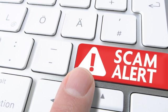 finger pressing red key labeled SCAM ALERT on computer keyboard