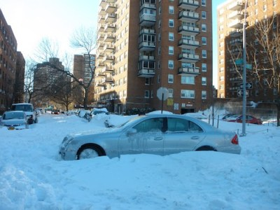This image shows a car stuck in the snow blocking the box in nyc