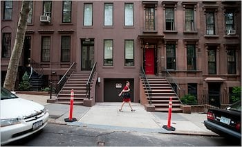 This is a NYC driveway with poles highlighting the entrance