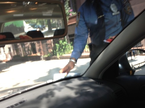 This is a parking ticket warrior placing a parking ticket under the wiper of a car