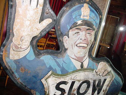 This is an image of a police officer holding a slow down sign