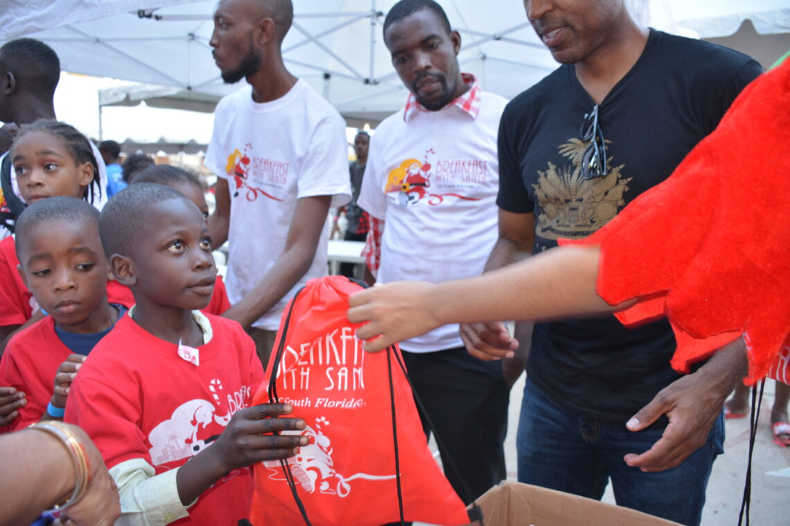 "Child receiving a gift at the Angels for Humanity ""Joy of Giving"" event"