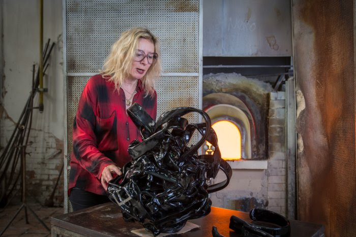 The Glasstress furnace in Venice blazes behind the artist Monica Bonvicini as she works on her glass sculpture Bonded.