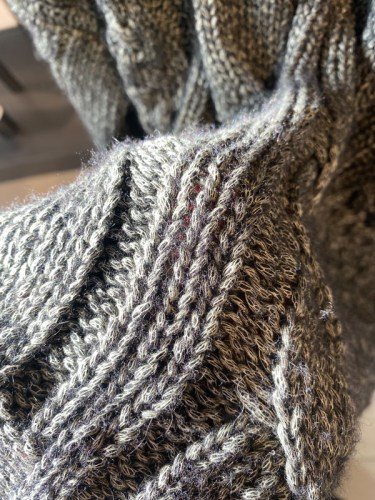 Macro of a sweater with intertwined color and fabrics with more blue tones visible