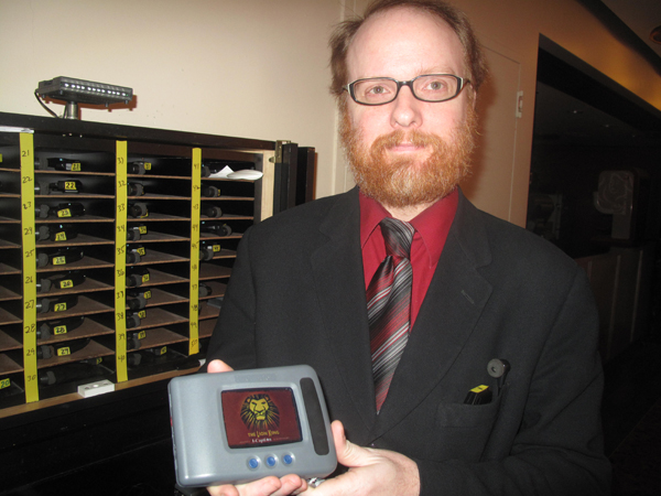 At The Lion King on Broadway, theater employee Rusty Thelin holds an i-Caption device in his hand. Behind him are infra-red assistive listening devices.