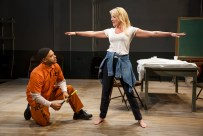 The volunteer (Sherie Rene Scott) getting the once-over with the metal-detecting wand by prison guard (Derrick Baskin)