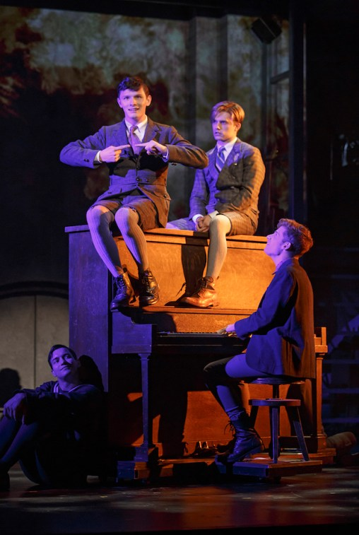 Joshua Castille and Andy Mientus on top of the piano Daniel David Stewart seated at the piano, Miles Barbee seated on the ground