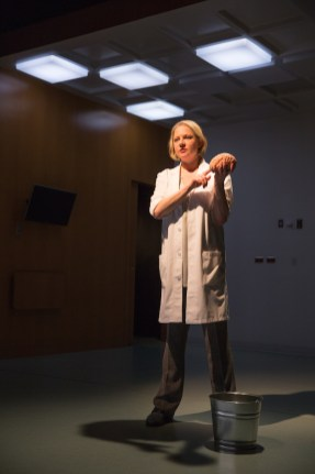 Kati Brazda as Dr. James, holding a brain