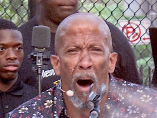 "Reg E. Cathey as Creon crying out in anguish in ""Antigone in Ferguson,"" presented for free by Theater of War Productions in a basketball court in Brownsville, Brooklyn. ""I am a foolish man…I am crushed, I have been crushed by fate,"""