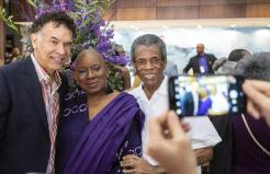 Brian Stokes Mitchell, from left, dancer Nana Malaya Rucker and Andre Dé Shields pose for a photo for a fan prior to the news conference kicking off the National Black Theatre Festival. Photo by Andrew Dye. Winston Salem Journal
