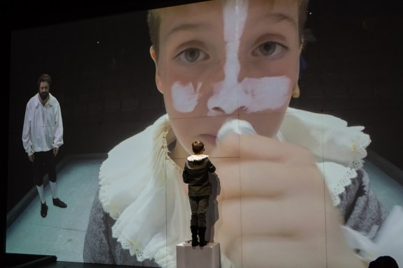 Aran Murphyas Hamnet, in person and projected onto the screen, along with Bush Moukarzel as his father Shakespeare