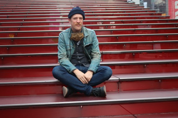 "Kevin James Doyle, co-star and co-creator of ""How 2 B a New Yorker"" which played at Planet Hollywood in Times Square, sitting on the near-empty red steps atop the TKTS ticket booth at the end of our tour of his favorite spots in Times Square."