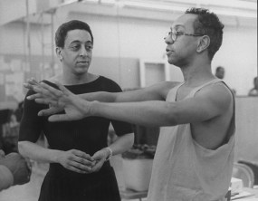 George C. Wolfe (right, seen here with the late Gregory Hines, left) is a playwright, director, and producer whose work has been seen in New York for over 35 years. Born in Kentucky, Wolfe saw his first Broadway show at age 13 and became determined to have a career in theatre. He gained attention in 1986 with the off-Broadway production of his play THE COLORED MUSEUM and went on to direct the Broadway productions of his musical JELLY'S LAST JAM (1992, pictured here in rehearsal w/Gregory Hines) and both parts of Tony Kushner's ANGELS IN AMERICA (1993). Wolfe was artistic director and producer of The Public Theater/New York Shakespeare Festival from 1993-2004 and has continued to direct on Broadway, most recently the 2019 production of Taylor Mac's GARY: A SEQUEL TO TITUS ANDRONICUS.