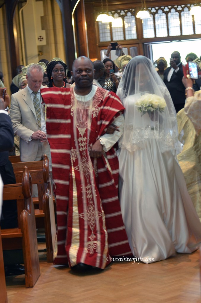 african dad walking daughter into church wedding