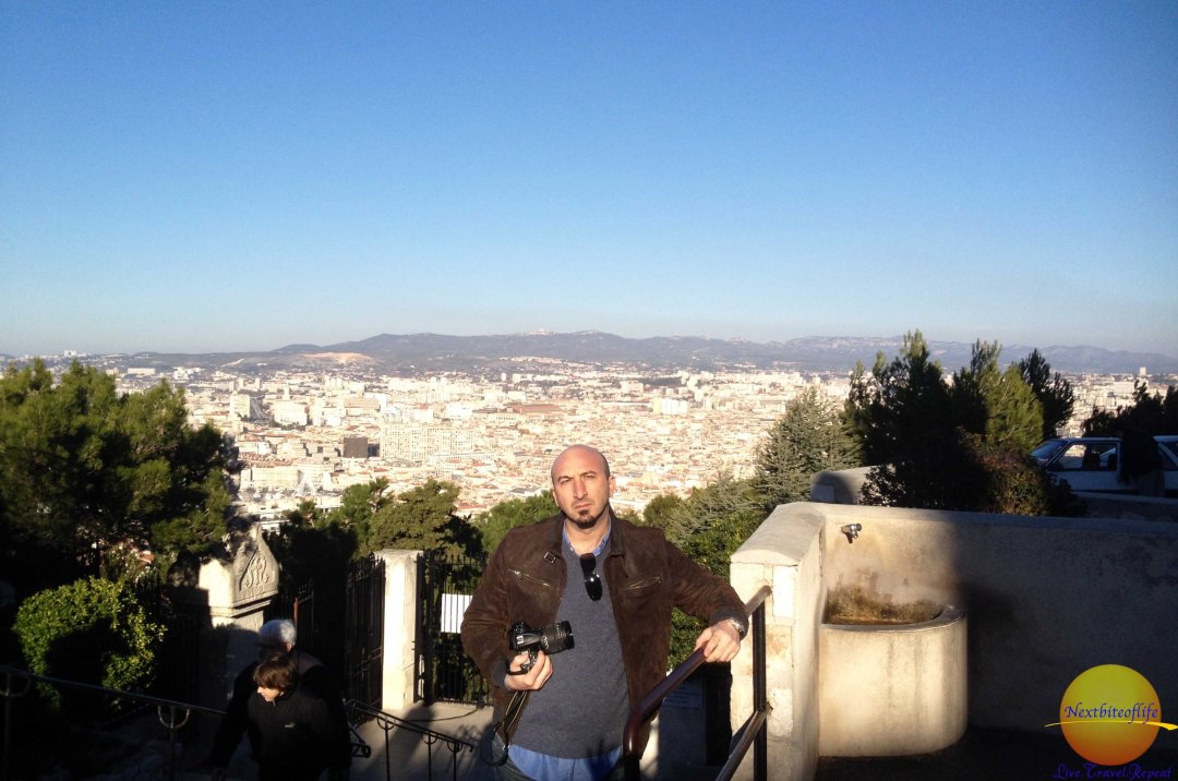 man at notre dame marseille with city view