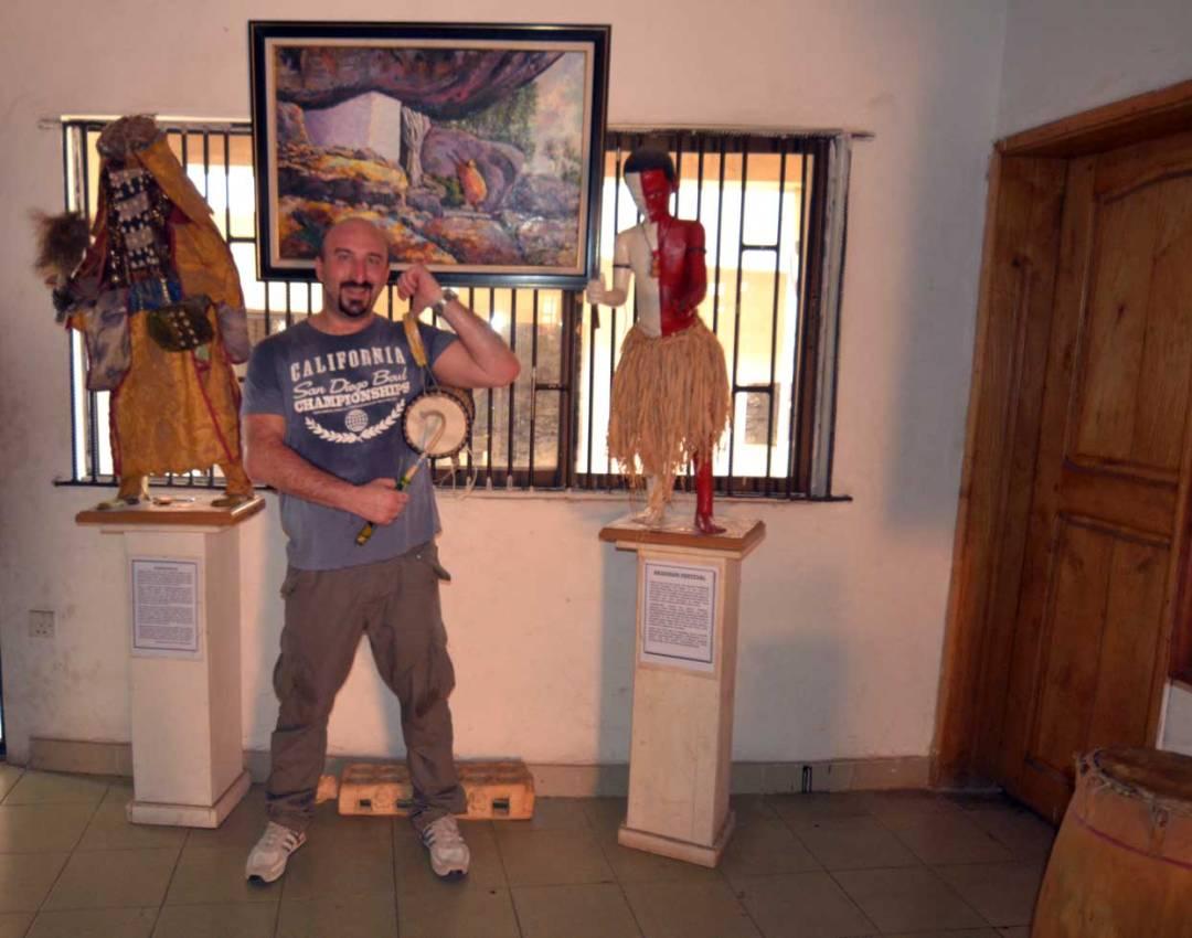 man holding talking drum olumo rock museum
