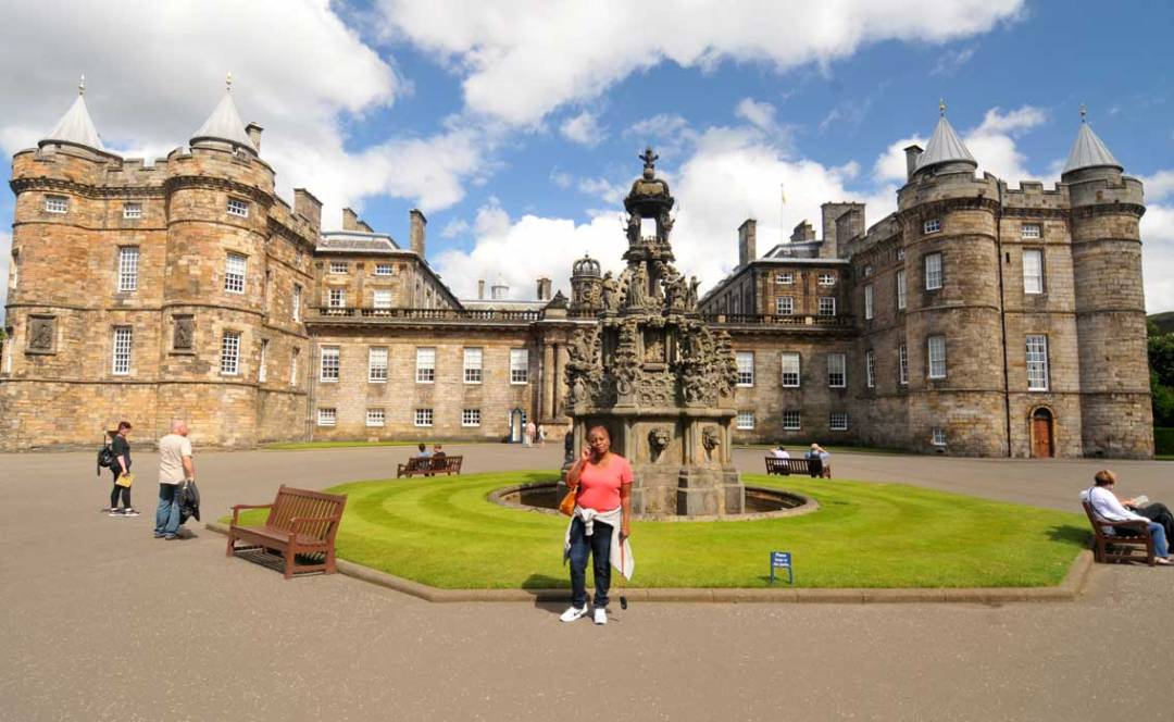 lady in fron of holyrood palace or palace of holyroodhouse