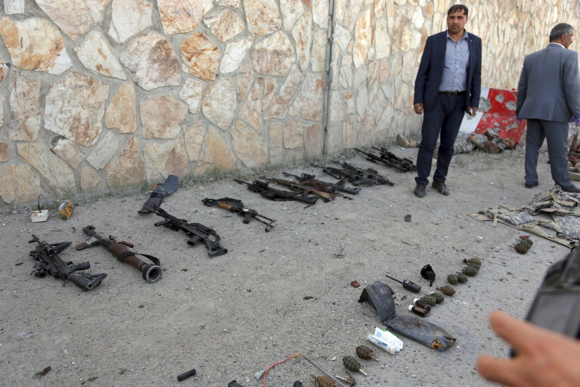 Security personnel display weapons and equipment used in an attack in Kabul.