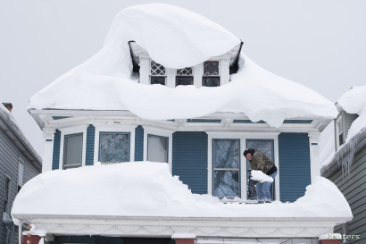Tom Wilczak shovels snow from the roof of his home following a storm in Buffalo, New York, Nov. 20, 2014.