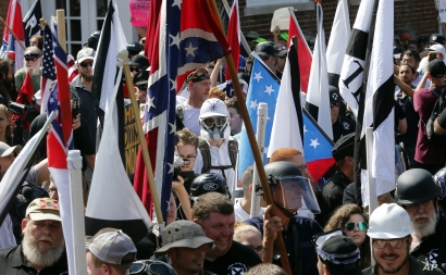 FILE - In this Saturday, Aug. 12, 2017 file photo, white nationalist demonstrators walk into the entrance of Lee Park surrounded by counter demonstrators in Charlottesville, Va. Conservative activists and leftist counter-protesters prepare for a…