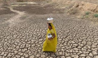 An Indian woman carriea an empty water pot as she crosses the dry bed of a pond at Mehmadpur village, some 20 kms from Ahmedabad on July 8, 2014. Western India's Gujarat state is bracing for a possible drought owing to very scant monsoon rains till date as the new government is due to present its first full budget on July 10, 2014, which economists expect to contain a credible outline of steps to steer India from a subsidy-laden, bureaucratic culture to a more business-friendly investment climate. AFP PHOTO / Sam PANTHAKYSAM PANTHAKY/AFP/Getty Images