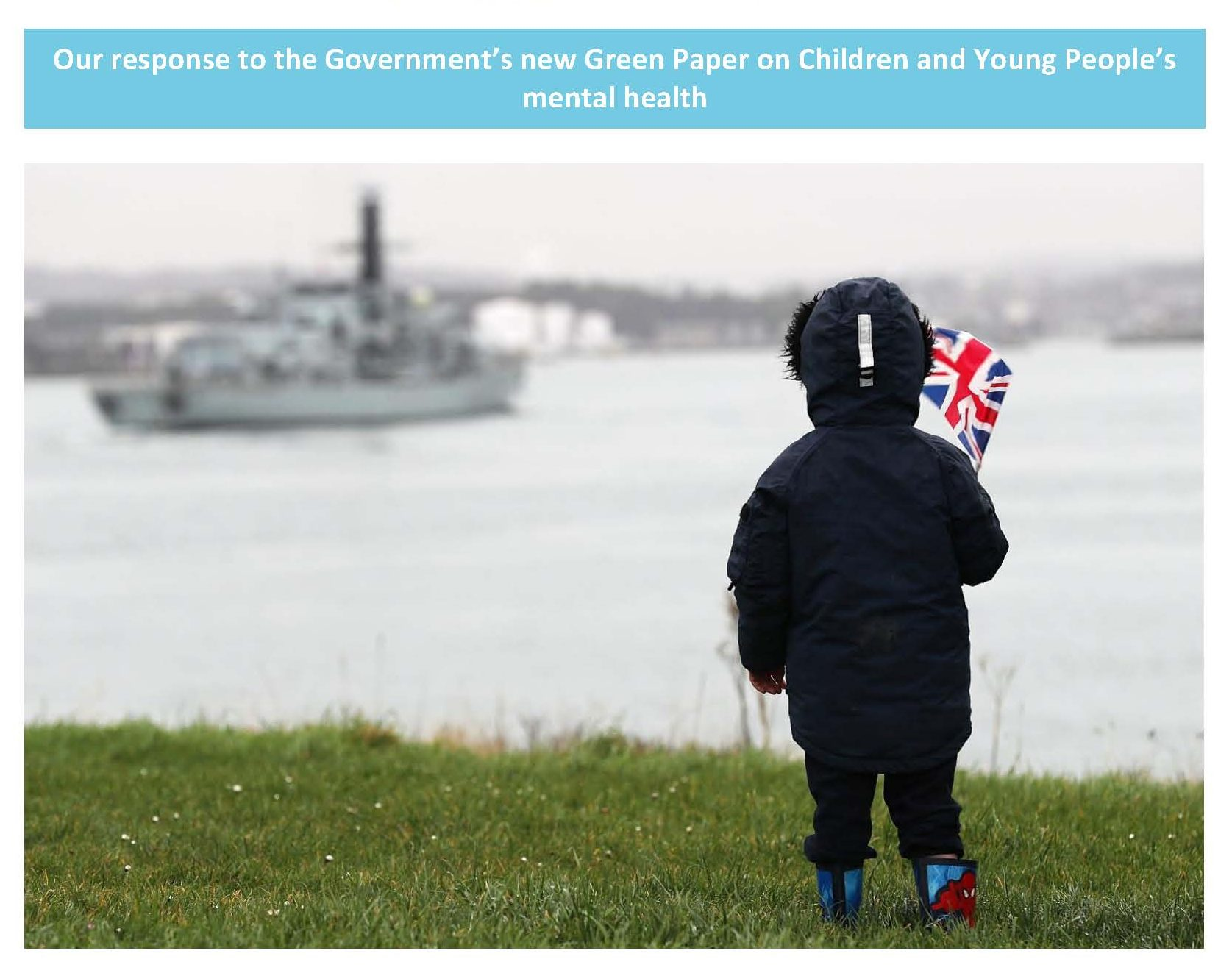 Child holding union flag looking out to see a ship coming in.
