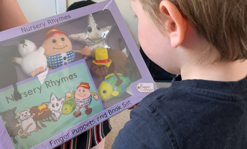 Boy looking at a nursery rhymes book and stuffed toys in a box