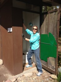 Suzanne cleaning the men's outhouse